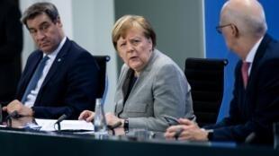 La chancelière allemande Angela Merkel (au centre) avec le Premier ministre de Bavière Markus Soeder, le 15 avril 2020. (à gauche) et le maire d'Hambourg Peter Tschentscher (à droite) lors d'une conférence de presse à Berlin, le 15 avril 2020.