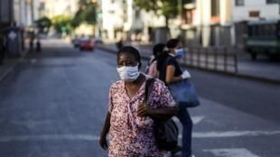 (illustration) Une femme porte un masque de protection contre le nouveau coronavirus dans les rues de Caracas, au Venezuela.
