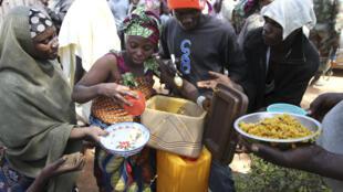 Au Nigeria, une femme partage sa nourriture dans un camp de déplacés (janvier  2010).