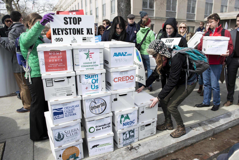 Des militants empilent des boîtes représentant une pétition signée par plus d'un million de personnes pour protester contre la construction du dernier tronçon de l'oléoduc Keystone XL. (Photo : 7 mars 2014 à Washington.)
