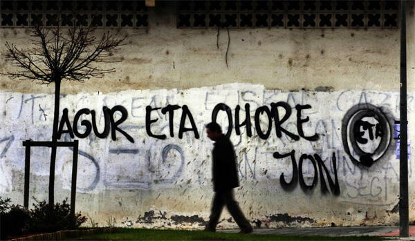 A man walks past graffiti and an ETA symbol in the Basque town of Guernica, Spain, on 14 March, 2010