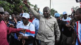 Freeman Mbowe, presidente de Chadema, saluda con el signo de la victoria a su llegada a la sede del partido tras ser excarcelado, el 14 de marzo de 2020 en Dar es Salaam