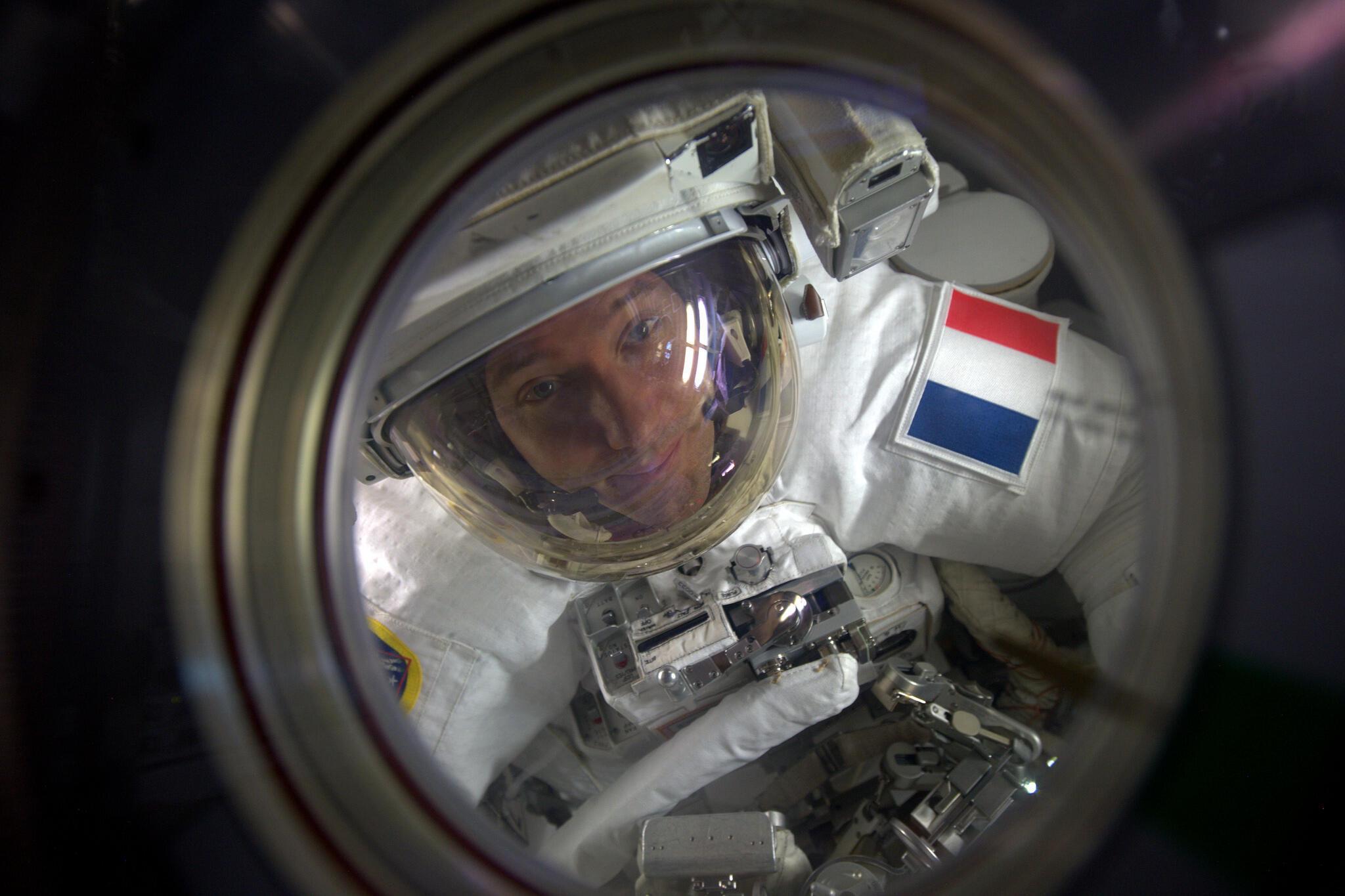 L'astronaute Thomas Pesquet dans le sas, à travers le hublot de la station spatiale internationale.