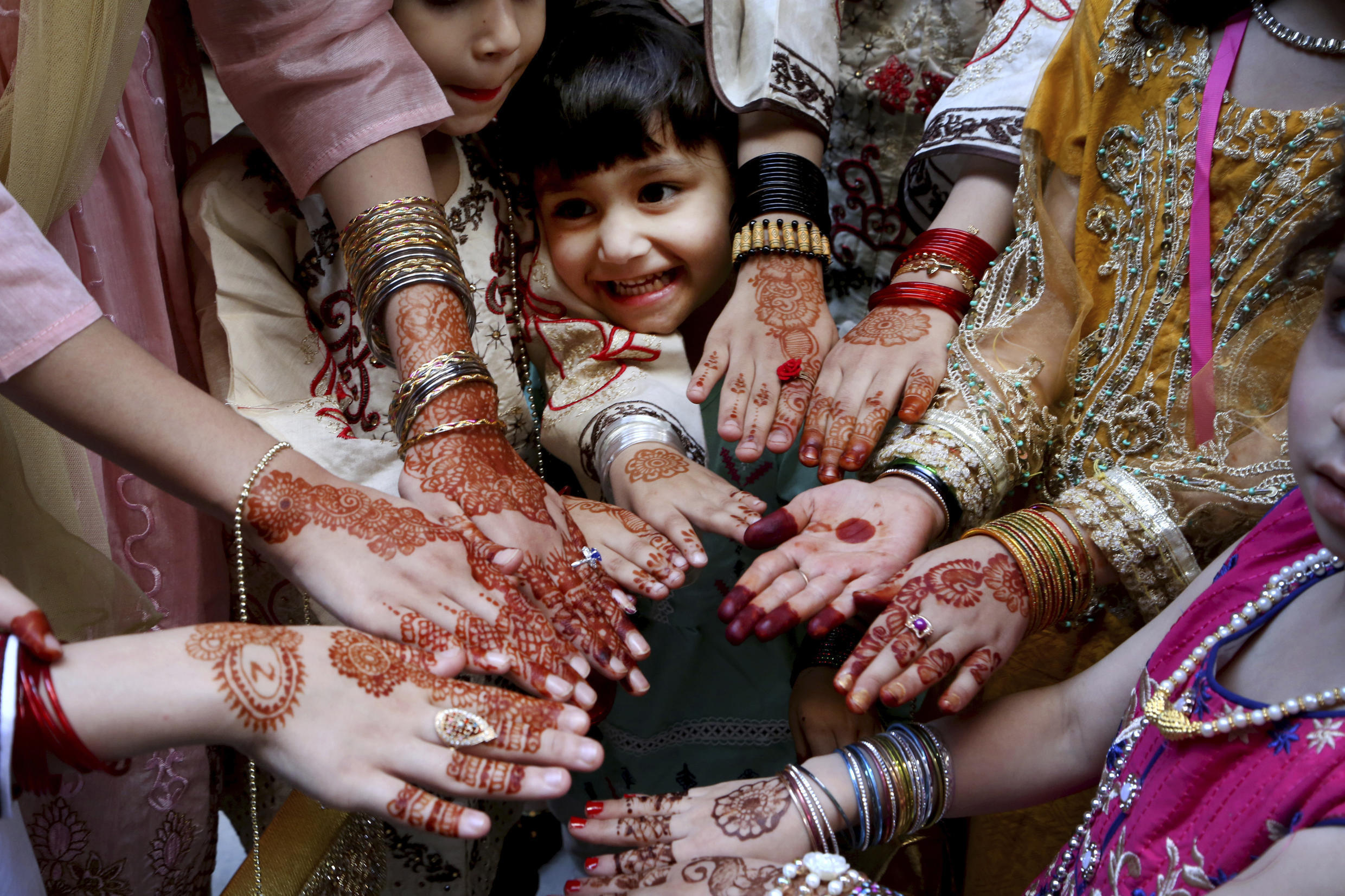 Muslim girls display their hands painted with traditional henna to celebrate Eid al-Fitr holidays, in Peshawar, Pakistan, 13 May, 2021.