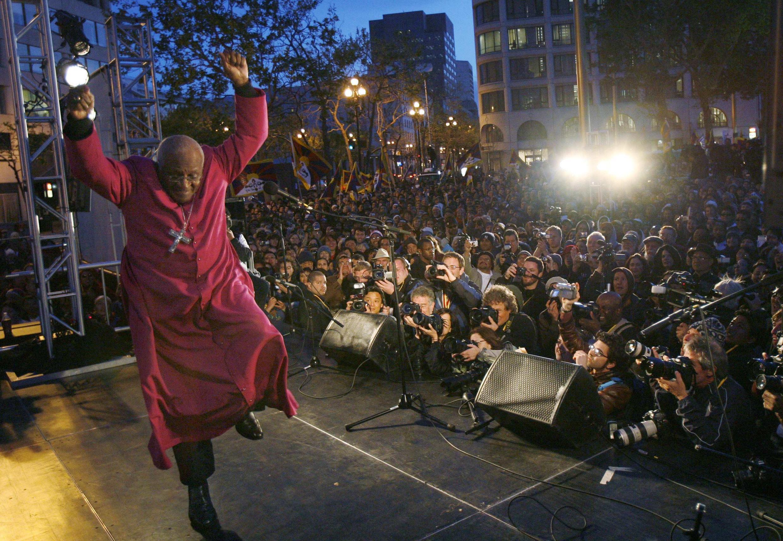 L'archevêque sud-africain Desmond Tutu, lauréat du prix Nobel de la paix, s'éloigne en dansant après avoir pris la parole lors d'un rassemblement pro-Tibet en 2008.