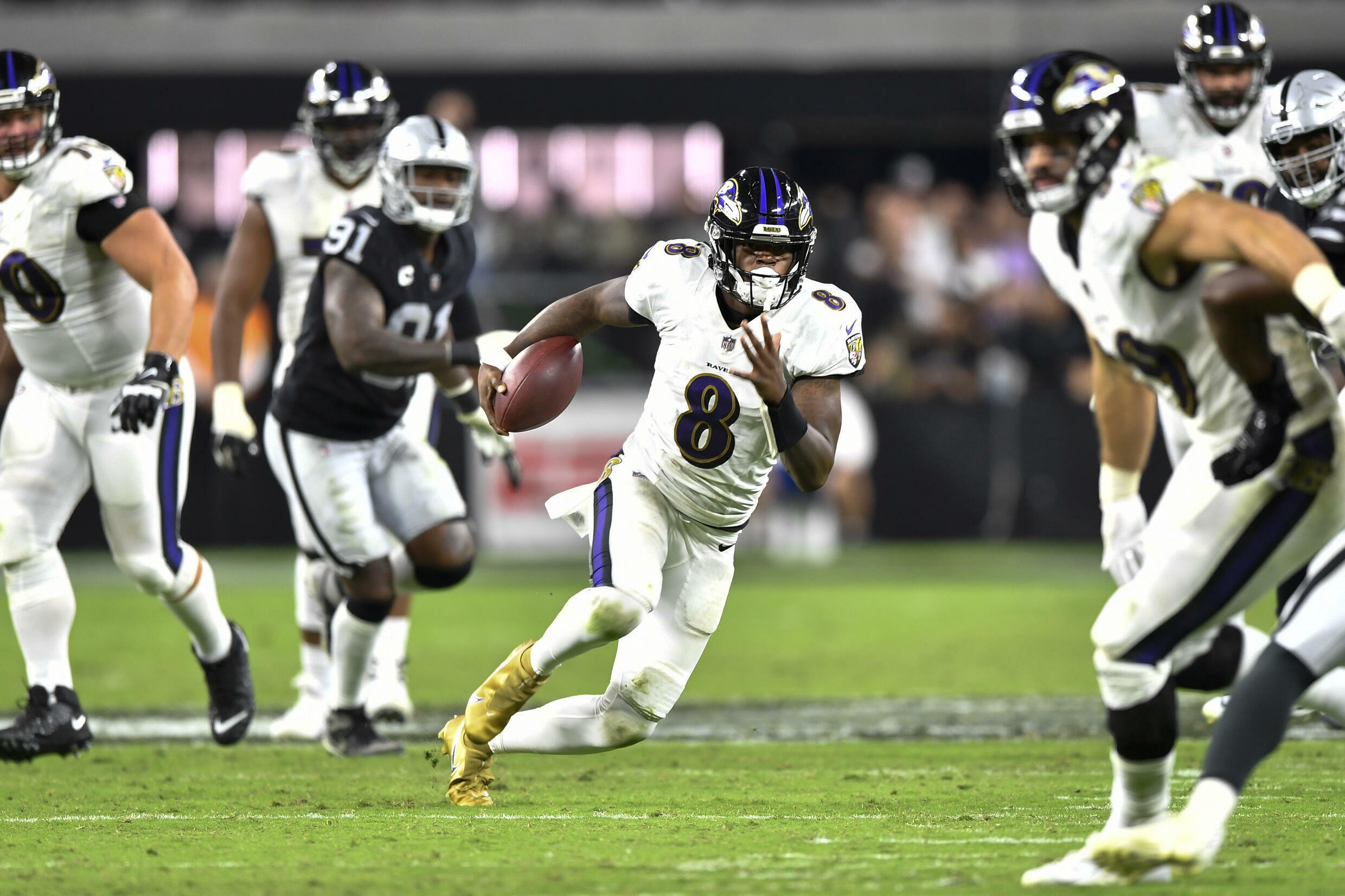 Baltimore Ravens quarterback Lamar Jackson, number 8, weaves his way through the Las Vegas defence in one of the most watched Monday Night Football week one contests in the past decade