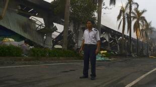 Một nhân viên an ninh trước cổng nhà máy Trung Quốc sản xuất giày bị đốt phá ở Bình Dương - REUTERS/Thanh Tung Truong