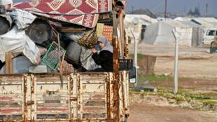 Des civils syriens partent de la région d'Idleb pour la frontière turco-syrienne, le 6 février 2020 près de la ville de Deir Ballut.