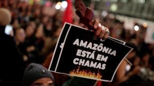 Manifestant brandissant une pancarte «l'Amazonie est en feu» durant une manifestation, à Sao Paulo, le 23 août 2019.