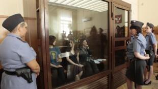 Les jeunes femmes de Pussy Riot dans leur cage de verre encadrées par leurs convoyeuses, le 8 août 2012.