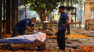 Un familiar de un fallecido por covid-19 en Nueva Delhi le rinde homenaje antes de su incineración, el 22 de abril de 2021