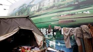 工人睡在房地产海报旁一个临时工棚,北京2011年7月15日