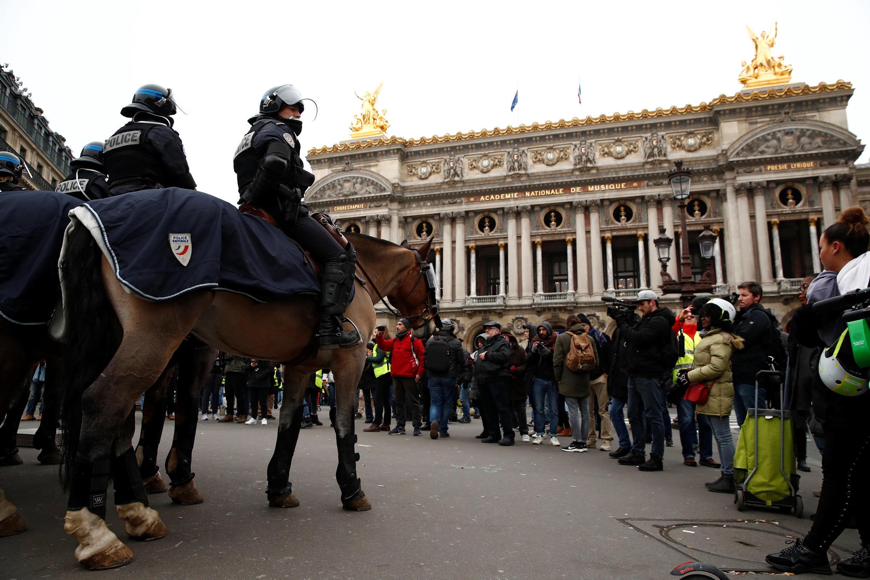 """Regimento da cavalaria cerca """"coletes amarelos"""" na praça da Ópera, em Paris."""