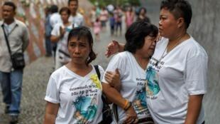 Des familles de pêcheurs du village de Baan Nam Khem en larmes pendant la commémoration des 10 ans du tsunami en hommage aux disparus, le 26 décembre 2014.