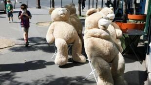 Des ours en peluche géants portent des masques, assis sur une chaise, dans une rue de Paris, le 23 avril 2020.