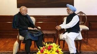 Indian Prime Minister Manmohan Singh (R) talks to Afghan President Hamid Karzai at Singh's residence in New Delhi