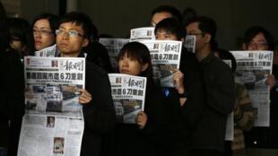 明报记者与编辑高举该报头版抗议暴力,2014年2月27日。