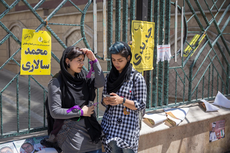 Cử tri tại Teheran theo dõi kết quả bầu cử tổng thống Iran qua điện thoại di động, ngày 17/05/2017.