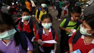 Crianças na saída de uma escola em Bancoc, na Tailândia, utilizam máscara contra a poluição.