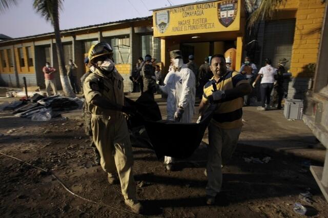 Bombeiros carregam cadáver na prisão de Comayagua, em 15 de fevereiro de 2012.