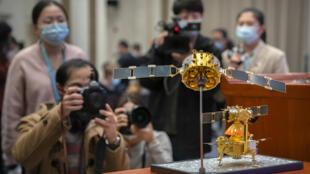 嫦娥5號探測器模型前,有記者在攝影。攝於12月17日。