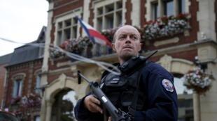 Полицейский возле мэрии Сент-Этьен-дю-Рувре после захвата заложников в местной церкви, Франция, 26 июля 2016 г.