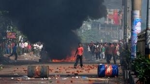 Bangladeshi garment workers light fires during a protest in Chittagong