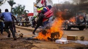 Mmoja wa wafuasi wa mwanamuziki Bobi Wine akibeba bango la lenye picha ya mpinzani huyo wakati wa maandamano ya kudai aachiliwe huru kwenye barabara ya jiji la Kampala, Novemba 18.