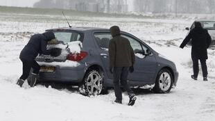 Passengers push a car stuck in snow near the French city of Lille