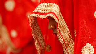 A bride waits to take her wedding vows during a mass marriage ceremony in Ahmedabad, India.