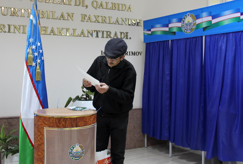 Một cử tri xem xét phiếu bầu tại một phòng phiếu ở Tashkent, thủ đô Uzbekistan, ngày 04/12/2016.