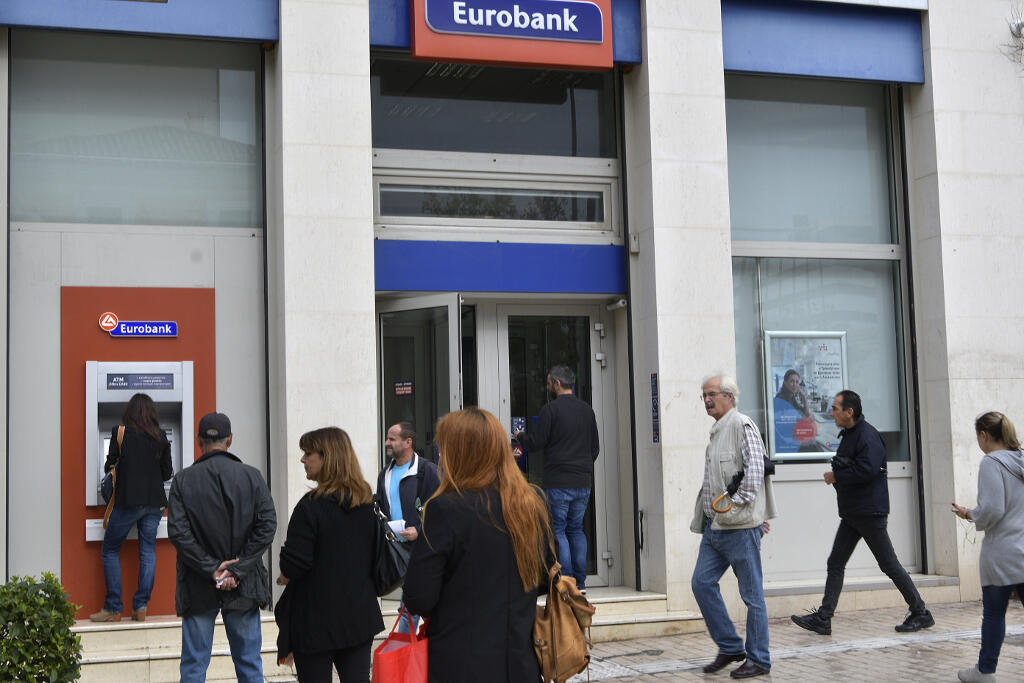 Le 1er octobre 2018, des personnes faisaient la queue au guichet automatique d'une banque située au centre d'Athènes, alors que la Grèce mettait fin aux contrôles de capitaux sur les retraits d'espèces sur son territoire.