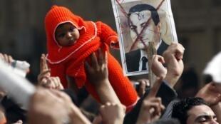 1月29日,埃及开罗的反政府游行中,一个游行者将一个婴儿举起来。这一天,执政30年的总统穆巴拉克终于在群众抗议示威的压力下,首次作出权利交接的举动, 任命了一名副总统。