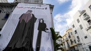 Une immense affiche sur laquelle apparaît la silhouette du prince, tronçonneuse à la main, et ces mots «Ne viens pas profaner la terre tunisienne de la révolution» habille la façade des locaux du syndicat des journalistes à Tunis, le 26 novembre 2018.