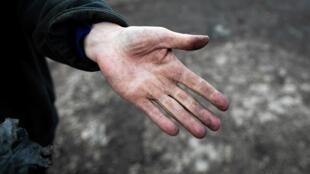 Agricultor mostra mão acizentada com o fumo do incêndio da fábrica de produtos químicos em Rouen, norte de França