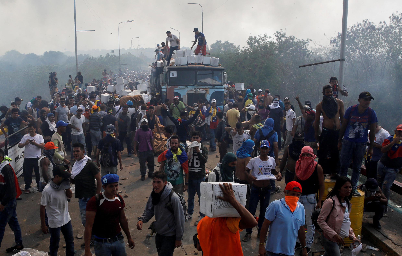 Un camion d'aide humanitaire est déchargé après avoir été incendié lors de heurts sur le pont Francisco de Paula Santander, à la frontière colombiano-vénézuélienne, le 23 février 2019.