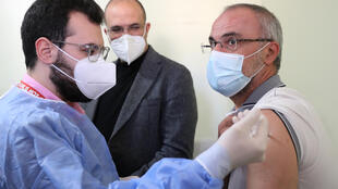 Lebanon's caretaker health minister Hamad Hassan watches as a teacher is vaccinated under the government's Covid inoculation scheme. For those who do not qualify but are ready to pledge their votes, there are politicians ready to provide the jabs