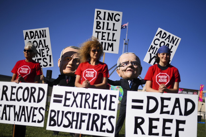 des manifestants portant des têtes de marionnettes géantes du Premier ministre australien Scott Morrison et du chef de l'opposition, Bill Shorten protestent contre le projet de mine de charbon du groupe indien Adani.