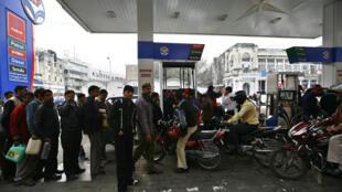 Des motards devant une station d'essence à New Delhi, le 9 janvier 2009.