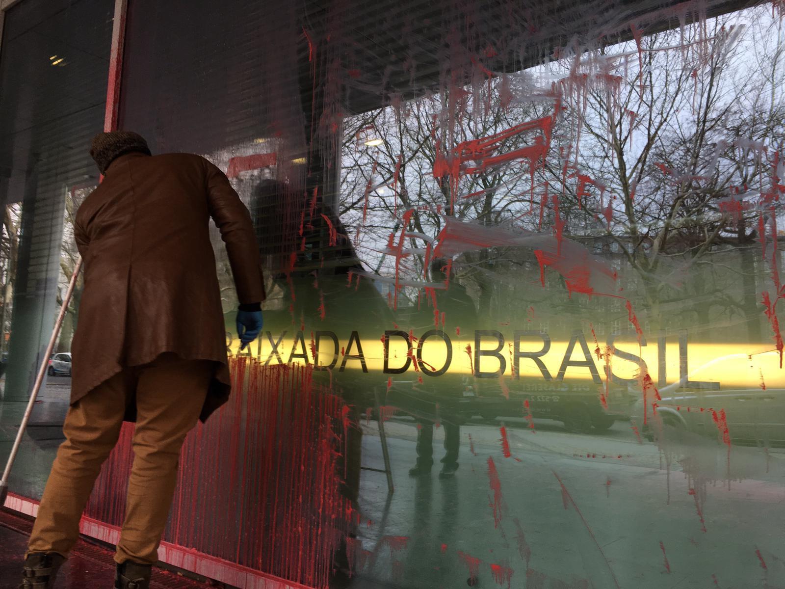 Funcionário limpa fachada da embaixada do Brasil em Berlim atingida por jatos de tinta vermelha.