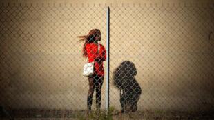 Une prostituée, derrière un grillage.