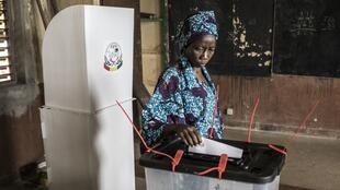A voter casts her ballot at a voting booth in a school during presidential elections in Conakry on October 18, 2020.