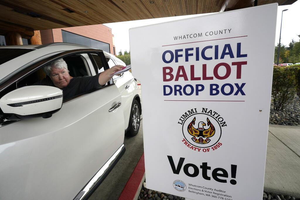 Lesley Beckley dépose son bulletin de vote complété dans une urne le lundi 19 octobre 2020, sur la réserve de Lummi, près de Bellingham dans l'État de Washington.