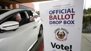 Uma eleitora americana deposita seu voto na urna. Em 19 de outubro de 2020, em Washington.