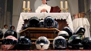 Священник Николя Мэн благословляет мотоциклистов в ходе воскресной мессы пригорода Парижа. 22 октября 2017 г.