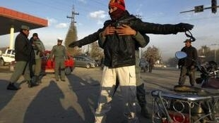 Stricy security - a passerby is searched as the loya jirga meets in Kabul