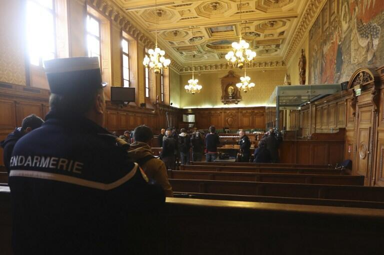 """A gendarme looks on (L) as reporters work next to a bulletproof dock in the courtroom of a Special Court of Assizes at the Paris courthouse, prior to the start of the trial of a jihadist cell known as the """"Cannes-Torcy cell"""""""