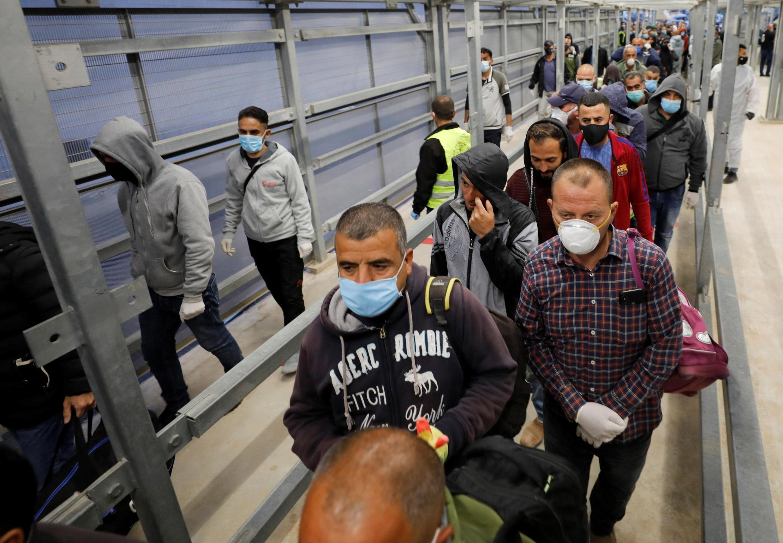 Des ouvriers palestiniens se rendent en Israël via un poste de contrôle près d'Hébron en Cisjordanie occupée, le 3 mai 2020.