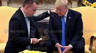 U.S. President Donald Trump closes his eyes in prayer along with Pastor Andrew Brunson, after his release from two years of Turkish detention, in the Oval Office of the White House, Washington, U.S., October 13, 2018.