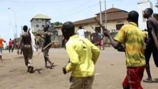 Des hommes portant des bâtons manifestent le long d'une rue de Conakry, le 23 mai 2013